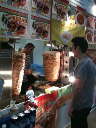 """Alex at our favorite Ghana food booth - check out the meat """"towers""""!"""